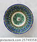 typical central asian bowl on gray concrete plate 25749358