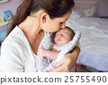 Beautiful mother holding newborn baby son in her 25755490