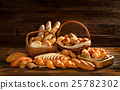 Variety of bread on old wooden background. 25782302