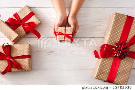 Woman's hands give christmas gift in present box 25783936