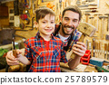 boy with dad holding chisel and hammer at workshop 25789579