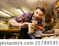 carpenter working with plane and wood at workshop 25789595