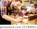dad and son with ruler measuring plank at workshop 25789601