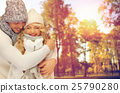 happy couple in warm clothes over autumn 25790280