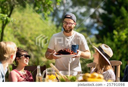 happy friends having dinner at summer garden party 25791098