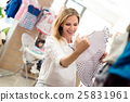 Pregnant woman shopping clothes for her baby 25831961