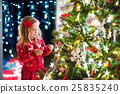 Child decorating Christmas tree 25835240