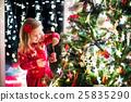 Child decorating Christmas tree 25835290