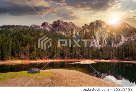 lake near the mountain in pine forest at sunset 25835458