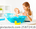 Happy family mother bathes the baby in  bath 25872416