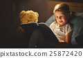 child girl reading a book in bed 25872420