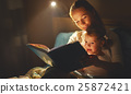 mother and child girl reading a book in bed 25872421