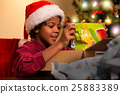 Black kid opening Christmas present. 25883389