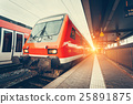 Modern high speed red commuter train at sunset 25891875