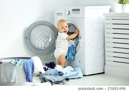 happy baby boy  to wash clothes and laughs in laundry 25892496