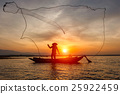 Silhouette fisherman with net at the lake 25922459