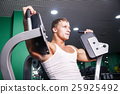 Athlete doing chest exercise on machine in gym 25925492