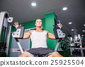 Athlete doing chest exercise on machine in gym 25925504