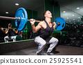 Sportsman squats in gym 25925541