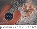ukulele with dried flower on old wooden background 25937326