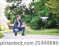Young hipster man with flying drone. Sunny green 25940680