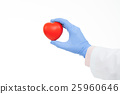 Doctor hand in a rubber glove holding toy heart 25960646