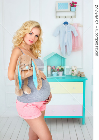 happy pregnant woman holds a plush toy 25964702