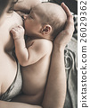 Soft photo young mother feeding breast her baby at home. 26029362