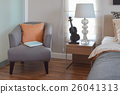 modern bedroom with orange pillow on grey chair 26041313