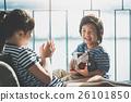 Asian girl playing ukulele near the window 26101850