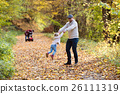 Beautiful young family on a walk in autumn forest. 26111319