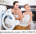 housewife and her daughter with linen near washing machine 26119635