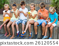 Busy children holding smartphones and sitting 26120554