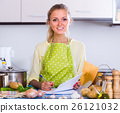 Housewife filling documents at kitchen. 26121032