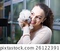 female customer watching fluffy chinchilla in petshop 26122391