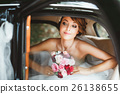Bride sitting in wedding car and looking at window 26138655