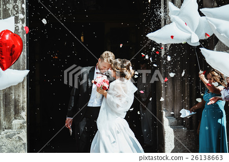 Bride and groom embracing near church  26138663