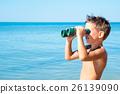 boy looks through binoculars and sees sea 26139090
