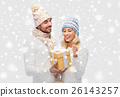 smiling couple in winter clothes with gift box 26143257