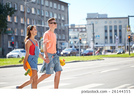 teenage couple with skateboards on city street 26144355
