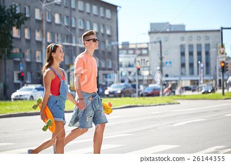 teenage couple with skateboards on city street 26144355