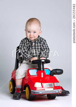 little boy driving toy car 26155482