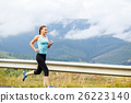 Young athletic woman jogging on road in mountains 26223140