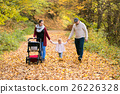 Beautiful young family on a walk in autumn forest. 26226328