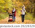 Beautiful young family on a walk in autumn forest. 26226329