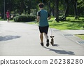 Taking a puppy to jog in the park in the morning 26238280