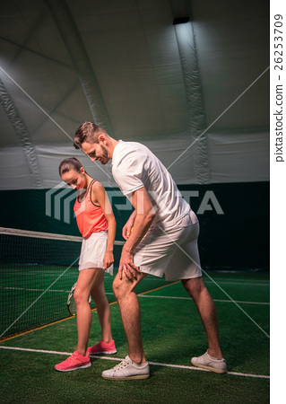 Positive tennis instructor teaching young woman 26253709