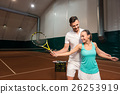 Positive professioanl tennis instructor showing a 26253919