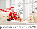 happy baby dressed as Santa Claus sitting on window of house in 26259296