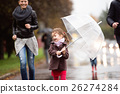 Little girl under the umbrella with her family 26274284